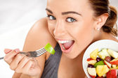 Slim young woman eating fruit salad — Stock Photo