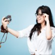 Attractive hipster photographer photographing self with retro camera — Stock Photo