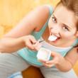 High key Portrait young caucasian woman eating yogurt at home — Stock Photo #15392395