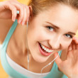Portrait of attractive young woman listening to music at gym — Stock Photo