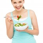 Young caucasian woman eating salad — Stock Photo