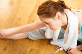 Healthy young sportswoman stretching at gym — Stock Photo