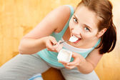 High key Portrait young caucasian woman eating yogurt at home — Stock Photo