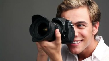 Happy young man using dslr digital camera taking photographs - studio shot