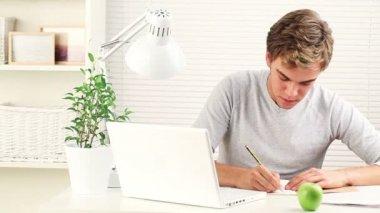 Heureux jeune étudiant étudie à domicile, à l'élaboration d'examens - à l'intérieur — Vidéo