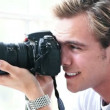 Gorgeous young man with camera - Stock Photo