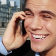 Happy businessman talking on mobile phone outdoors in the city — Stock Video