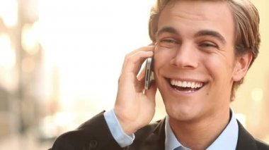 Happy young businessman talking on mobile phone outdoors — Stock Video