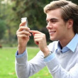 Attractive young student is happy using mobile phone sending text message in park - outdoors — Stock Video #15440589