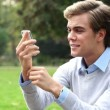 Happy young man using talking on mobile phone outdoors — Stock Video #15440697