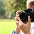 Attractive young male photographer using dslr digital camera taking photographs outdoors in the park in the sunshine — Stock Video #15440771