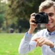 Attractive young male photographer using dslr digital camera taking photographs outdoors in the park in the sunshine — Stock Video #15440797