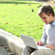 Attractive young student is happy using laptop in park - outdoors - Stock Photo