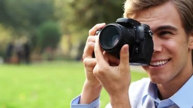 Joyful young photographer guy using dslr camera outdoors — Stock Video #15440811