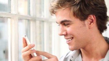 Joyful young man sending text message using smartphone - indoors — Stock Video