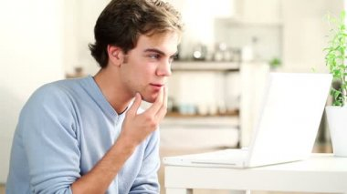 Attractive successful young man is excited winning online