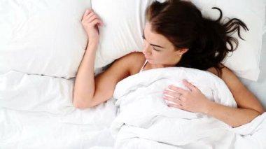 Atrakcyjna młoda kobieta budzi się w łóżku w domu — Wideo stockowe