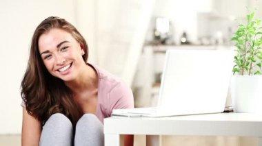 ホーム カメラ目線と笑みを浮かべて座っているきれいな若い女の子 — ストックビデオ