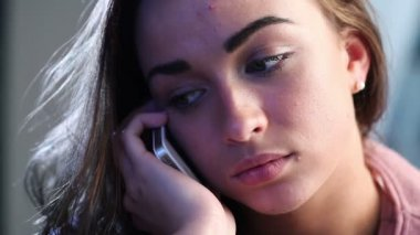 Depressed young woman contemplates suicide as she hears bad news over the phone at home