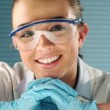 Pretty young chemistry student smiling in laboratory — Wideo stockowe