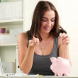 Happy teenager saving money in her piggy-bank - indoors — Stock Video #15658649
