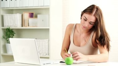 Close-up portrait of cute young woman eating green apple at desk
