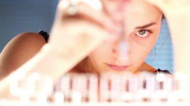 Jeune fille à l'aide d'une pipette et tubes à essai dans un laboratoire — Vidéo