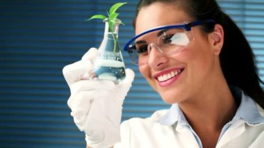 Student standing at the laboratory while smiling and holding a plant — Stock Video
