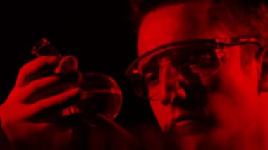 Scientist examining the flask with the liquid in the dark labaratory — Stock Video