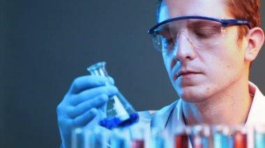 Young scientist mixes liquids — Stock Video