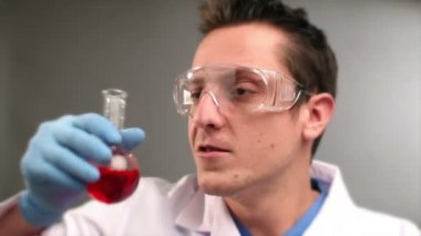 Scientist drinking red liquid in the labaratory — Stock Video