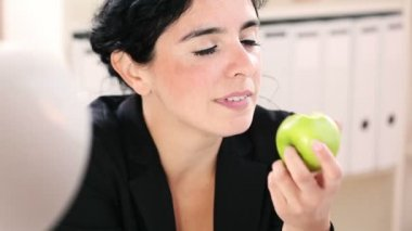 Smiling businesswoman eating an apple in the office — Stock Video