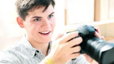 Joven mirando fotos a través de la pantalla de cámara — Vídeo de stock