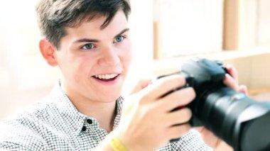 カメラ画面を介して写真を見て若い男 — ストックビデオ