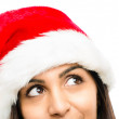 Close up of pretty woman wearing christmas hat looking up isolat — Stock Photo #19473925