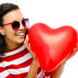 Pretty mixed race girl holding red heart balloon — Stock Photo