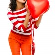 Pretty mixed race girl holding red heart balloon — Stock Photo #27386511