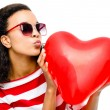 Pretty mixed race girl holding red heart balloon — Stock Photo #27394953