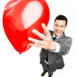 Stock Photo: Businessman holding red heart balloon