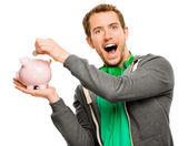 Heureux jeune homme, mettre de l'argent dans la tirelire isolé sur blanc — Photo