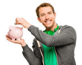 Happy young man putting money in piggy bank isolated on white — Stock Photo