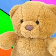 Teddy bear on a wooden colorful background — Stock Photo