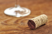 Cork and glass of Italian red wine on a table in oak — Stock Photo
