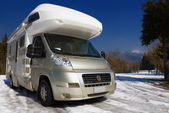 Camper parked on snow in the mountain — Stock Photo
