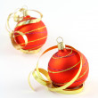 Stock Photo: Two red Christmas tree balls with curly ribbons on white background
