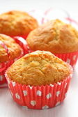 Muffins in red cups on white — Stock Photo