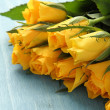 Bouquet of yellow roses on blue background — Stock Photo