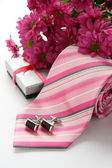 Tie and cuff links with flowers over white — Stock Photo