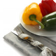 Stockfoto: Measuring tape wrapped around cutlery with paprica over white