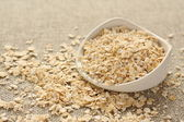 Oat flakes in white ceramic bowl on sackcloth background — Stock Photo